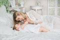 Portrait Of Young Mother Plays With Her Little Baby On A Bed Stock Image - 91838721
