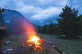 Burning Camp Fire Into Remote Larch And Pine Tree Woodland With High Altitude Landscape And Dramatic Sky At Dusk. Summer Adventure Stock Photos - 91915963