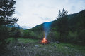 Burning Camp Fire Into Remote Larch And Pine Tree Woodland With High Altitude Landscape And Dramatic Sky At Dusk. Summer Adventure Stock Photos - 91916023
