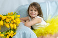 Happy Little Girl Sitting On The Sofa Near The Big Bouquet Of Tu Stock Photo - 91947050