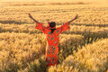 African Woman In Traditional Clothes Arms Raised In Field Of Cro Royalty Free Stock Photo - 92055515