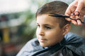 Little Boy Getting Haircut By Barber While Sitting In Chair At Barbershop. Royalty Free Stock Image - 92069246