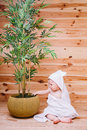 The Baby Wrapped In A White Towel Sitting On Wooden Background Near A Bamboo Tree In Pot Royalty Free Stock Photo - 92131325
