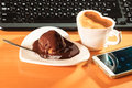 Cup Of Coffee And Chocolate Cake Next To Computer. Royalty Free Stock Photography - 92154347