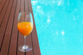 Orange Juice In Wine Glass On Edge  The Blue Sky Pool In Party L Stock Image - 92249481