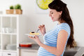Happy Pregnant Woman Eating Cake At Home Kitchen Stock Photography - 92249932