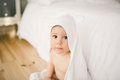 Newborn Baby Five Month Old Baby In The Bedroom Next To A Large White Bed On The Wooden Floor Wrapped In A White Bamboo Towel. Stock Photos - 92254663