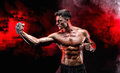 Serious Muscular Fighter Doing The Punch With The Chains Braided Over His Fist. Royalty Free Stock Photo - 92264045