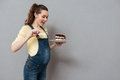 Portrait Of An Excited Young Pregnant Woman Eating Chocolate Cake Royalty Free Stock Photography - 92308437