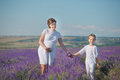 Young Beautiful Lady Mother With Lovely Daughter Walking On The Lavender Field On A Weekend Day In Wonderful Dresses And Hats. Royalty Free Stock Image - 92449566