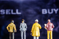 Miniature Figurine Starring At Big Defocused Sell And Buy Words Stock Photos - 92472733