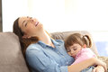 Tired Mother Sleeping With Her Baby Daughter Royalty Free Stock Image - 92530326