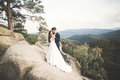 Wedding Couple In Love Kissing And Hugging Near Rocks On Beautiful Landscape Stock Photos - 92581153