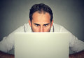Man Hiding Behind A Laptop Staring At Screen With A Shocked Face Expression Royalty Free Stock Photo - 92749545