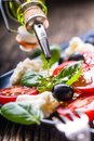 Caprese Salad.Mediterranean Salad. Mozzarella Cherry Tomatoes Basil And Olive Oil On Old Oak Table. Italian Cuisine Stock Photos - 92784163
