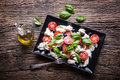 Caprese Salad.Mediterranean Salad. Mozzarella Cherry Tomatoes Basil And Olive Oil On Old Oak Table. Italian Cuisine Royalty Free Stock Images - 92784169