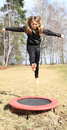 Blond Girl Jumping On Trampoline Stock Photo - 92797480