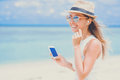 Young Sexy Woman With Earphones Using Phone On The Beach Royalty Free Stock Photography - 92811537