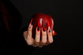 Hands With Scary Nails Manicure Holding Poisoned Red Apple Stock Image - 93000021