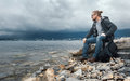 Man Traveler With A Backpack Seets On The Seashore Against A Background Of Clouds And A Mountain Range Concept Of Hiking Stock Image - 93083701