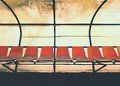 Vintage Plastic Seats On Outdoor Stadium Players Bench, Chairs With Worn Paint Below Roof. Royalty Free Stock Image - 93093586