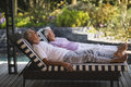 Full Length Of Senior Couple Resting Together On Lounge Chairs Royalty Free Stock Image - 93246556