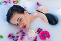 Sexy Brunette Woman Relaxing In Hot Milk Bath With Flowers Royalty Free Stock Image - 93311556