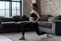 Pretty Fit Woman Doing Frontal Lunges Or Squat Exercise Indoors In A Flat Royalty Free Stock Image - 93312176