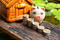 Stack Coins Beside Piggy Bank And Front Of Mini House For Financ Stock Images - 93352584