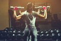 Slim Bodybuilder Girl Lifts Heavy Dumbbell Standing In Front Of The Mirror While Training In The Gym. Royalty Free Stock Photography - 93393897