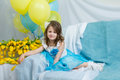 The Little Girl On The Sofa With A Bouquet Of Flowers. Royalty Free Stock Photos - 93455618