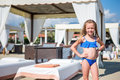Adorable Happy Smiling Little Girl On Beach Vacation Near Sunbeds Royalty Free Stock Photography - 93458317