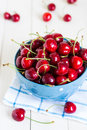 Red Cherries In Bowl On White Wooden Background On Blue Towel Royalty Free Stock Photo - 93500165