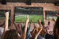 Rear View Of Friends Watching Game In Sports Bar On Screens Royalty Free Stock Photo - 93531365