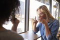 Two Female Friends Meeting In Coffee Shop Royalty Free Stock Photo - 93542075