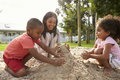 Teacher At Montessori School Playing With Children In Sand Pit Royalty Free Stock Images - 93542679