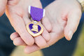 Senior Man Holding The Military Purple Heart Medal In His Hands. Royalty Free Stock Image - 93655296