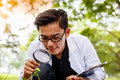Asian Biotechnology Scientist Working Examining Plants At Forest Stock Images - 93662304