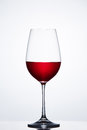 Red Wine In The Fragile Pure Wineglass Standing Against Light Bckground With Reflection. Stock Photo - 93750010
