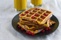 Appetizing Fried Pumpkin Viennese Wafers With Cranberry Berries On A Black Plate On Cotton Sackcloth With Yellow Glasses Of Coffee Stock Images - 93799664