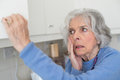 Forgetful Senior Woman With Dementia Looking In Cupboard Stock Photography - 93812762