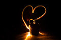 Two Young Lovers Paint A Heart On Fire. Silhouette Of Couple And Love Words On A Dark Background Royalty Free Stock Images - 93832869