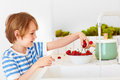 Cute Young Boy Washing The Armful Of Sweet Cherries Under Tap Water In The Kitchen Royalty Free Stock Photos - 93853408