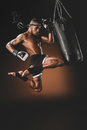 Side View Of Concentrated Muay Thai Fighter Training With Punching Bag Royalty Free Stock Photo - 93854995