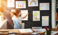Child Girl Hanging Her Drawings On Wall Stock Photo - 93901680