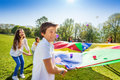 Boy Throwing Balls Up By Using Rainbow Parachute Royalty Free Stock Photo - 93928505