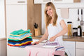 Smiling Woman Ironing Clothes With Electric Iron Royalty Free Stock Image - 94050606