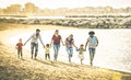 Happy Multiracial Families Running Together At Beach At Sunset Royalty Free Stock Photo - 94183295