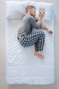 Peaceful Nice Man Putting The Alarm Clock On The Pillow Royalty Free Stock Images - 94240039