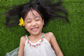 Asian Chinese Little Girl Lying On The Grass With Flower Stock Image - 94315891